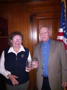 Lois receiving an SRC mug from President Austin.